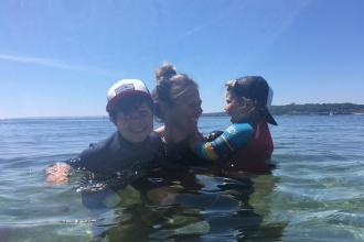 Marine Team Officer Abby Crosby bobs in the water with her two young children, surrounded by clear,calm blue waters and a bright blue sky behind. They are all laughing happily and enjoying the sun and the sea.