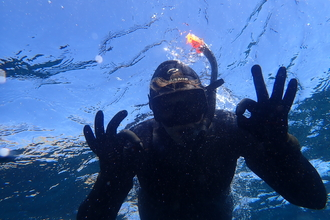 "the silhouette of a snorkeler signing ""ok"" as they swim through crystal clear water"