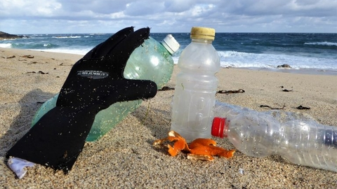 Wetsuit glove and plastic bottles on a Cornish beach