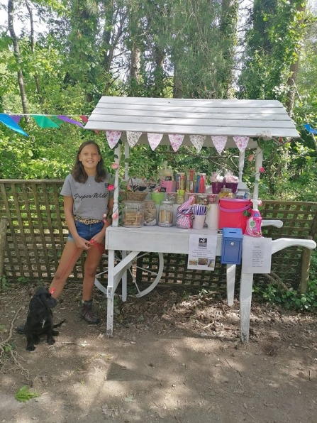 Izzy, 13, stands proudly by her sweet stall on the bissoe trail