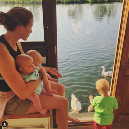 Helen sits to the left of the image, with her two twins perched on her knee. Her young son brogan is at her feet, looking out of a door way to feed the ducks on the river below. The sun streams onto them and the river shimmers