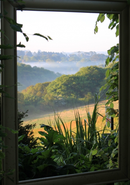 looking from a window onto a picturesque pastoral landscape of green and yellow rolling hills and a misty sky