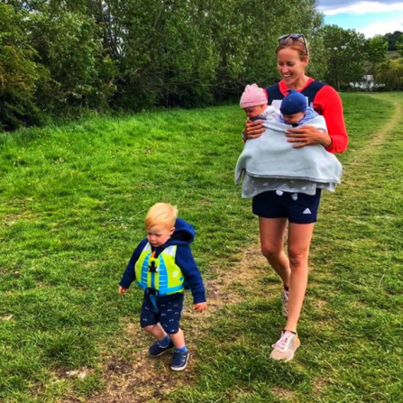 Helen walks along a path with her twins carried on her chest, as her young son logan runs ahead in blue shorts and a life jacket